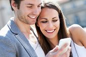 image of sms  - Smiling couple with mobile phone - JPG
