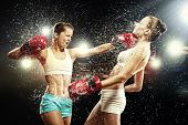 image of boxing ring  - Two young pretty women boxing standing against flashes background - JPG