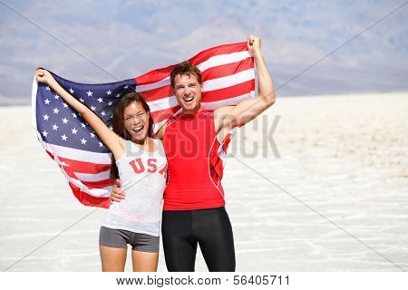 USA athletes people holding american flag cheering. Sports man and fitness runner woman celebrating winning after running. Happy young multicultural fitness couple in excited celebration outside.