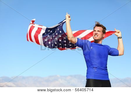 Athlete cheering holding US flag motivated athletic young man standing with the American flag raised in the air in his hands blowing in the breeze against a clear sunny blue sky
