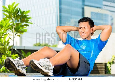 Urban sports - young Asian Indonesian man is doing warming up and sit-ups before running in the city on a beautiful summer day