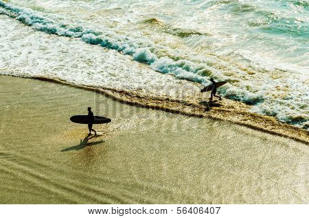 Two surfers going back to the beach