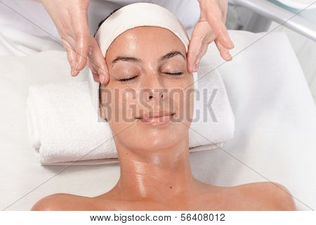 Young woman getting facial massage in beauty saloon, laying relaxed.