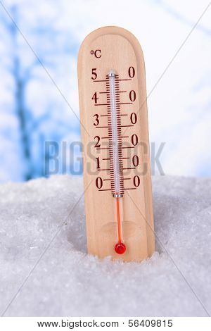 Thermometer in snow on light background