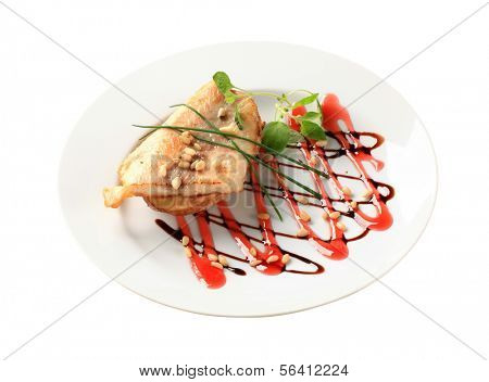 Pan-fried fish fillet on baked potato garnished with balsamic sauce and pine nuts