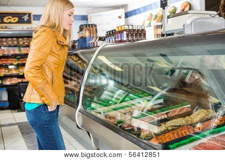 Side view of female customer selecting meat at butcher's shop