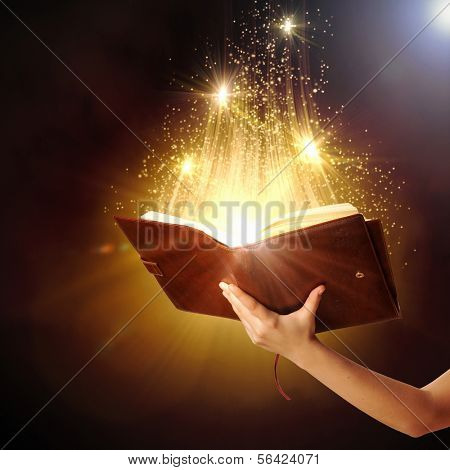 Human hand holding magic book with magic lights