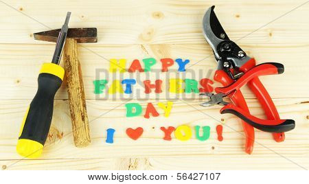Happy Fathers Day (concept image with multicolor letters and tools, on wooden background)