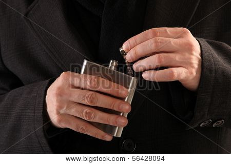 Hip flask with liquor is opening by hands