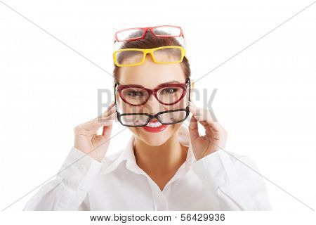 Beautiful woman wearing four different pairs of eyeglasses. Isolated on white.