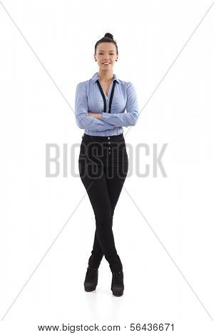 Happy woman standing arms and legs crossed, full size.