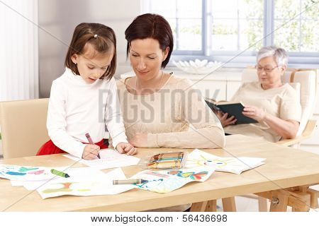 Mother and little daughter drawing by table. Granny at background.