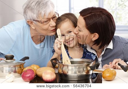 Mother, grandmother and little daughter cooking together at home, all smiling.