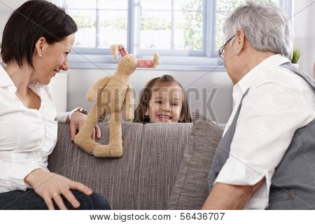 Little girl presenting puppet show to mother and granny, all smiling.