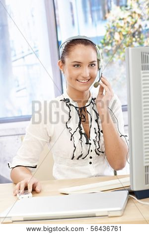 Happy callcenter operator girl at desk, using headset, working with desktop computer, smiling.