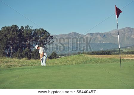 Golfer hitting chip shot from off the green in the rough on scenic golf course