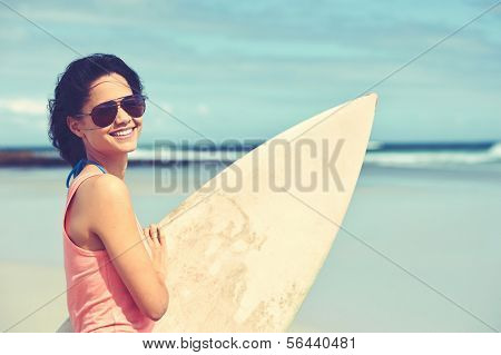 Portrait of happy young woman with surfboard at the beach