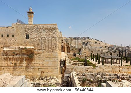 Minaret of Al-Aqsa Mosque surrounded by walls and ancient ruins in Old City of Jerusalem, Israel.