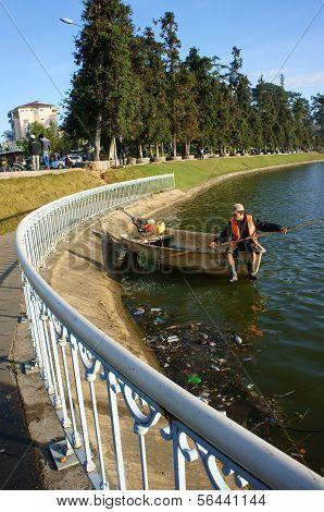 Vietnamese Sanitation Worker Pick Up Trash On Lake