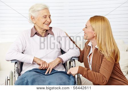 Caregiver woman talking to senior citizen in wheelchair at home