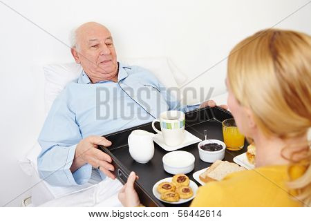 Woman giving breakfast to senior citizen in bed at home