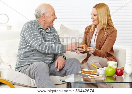 Family with senior citizen eating breakfast together at home