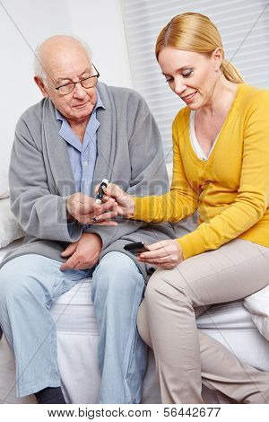 Woman doing blood glucose monitoring for senior man at home