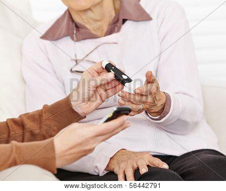 Blood sugar measurement in hand for senior citizen woman