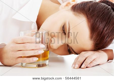 Young beautiful business woman with glass of whisky or rum. Isolated on white.