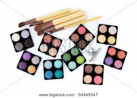 Various eyeshadow palettes, fake eyelashes and cosmetic brushes, isolated on white