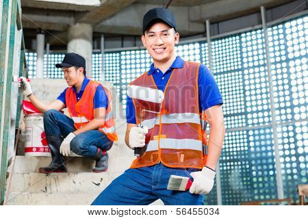 Asian Indonesian painter paint with a brush, paint roller, color and tools in gumboots or rubber boots and protection gloves the walls of a tower building or construction site