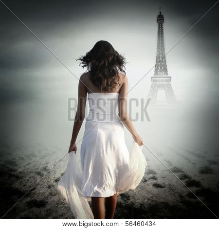 Rear view of young woman walking in front of Eiffel Tower in Paris