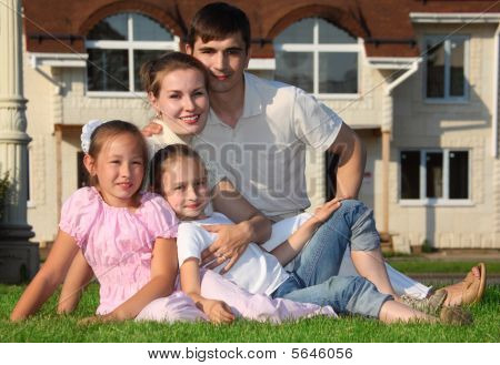 Family From Four Sits On Grass Against House