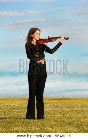 Girl Stands On Grass And Plays Violin Against  Sky