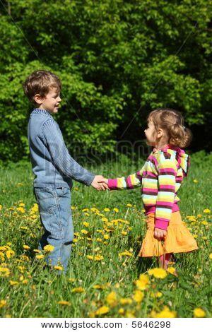 jungen und Mädchen Handshaking unter blühenden Löwenzahn