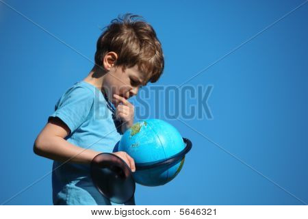 Boy Looks On Globe Against Sky