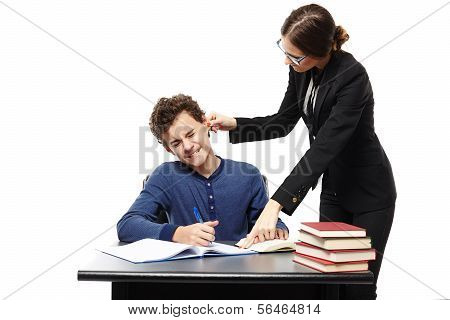 Angry Teacher Twisting The Student's Ear And Pointing Him Something In His Notebook