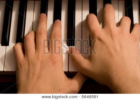 Two hands on a piano keyboard