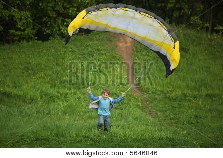 Boy Runs From Hill With Parachute