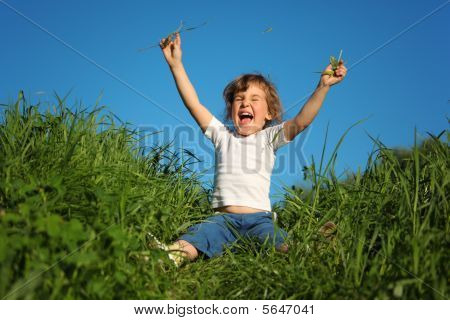 Smiling Little Girl Sits In Grass With Lifted Hands