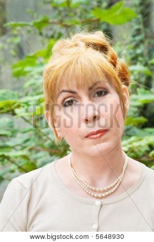 Woman with red hair in the garden
