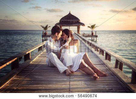 Happy loving couple in white clothes posing on a pier on Maldives