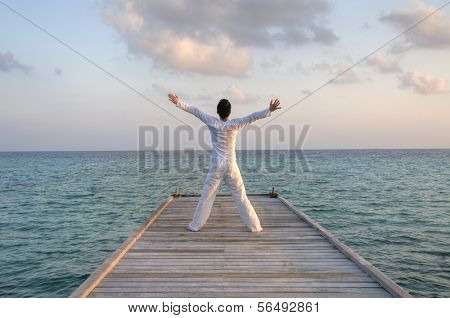 Caucasian man in white clothes standing on a pier on Maldives