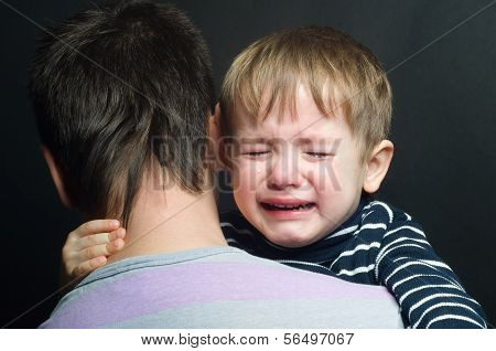 Crying child in the arms of his father