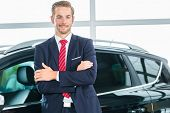 Постер, плакат: Продавец или автомобиля продавец в автосалон представляя его новых и подержанных автомобилей в салоне