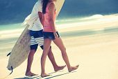 stock photo of board-walk  - Hispanic couple walk on beach together with surfboard having fun outdoors - JPG
