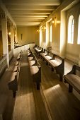 stock photo of pews  - Warm natural light on lines of church pews at place of worship - JPG