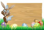 image of easter decoration  - Cartoon Easter rabbit bunny pointing at a sign decorated Easter eggs and basket in front - JPG