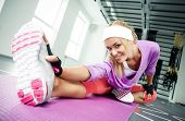 stock photo of joint  - Smiling athletic woman stretches the muscles in a gym - JPG