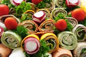 foto of sandwich wrap  - Closeup on platter of assorted meat tortilla wraps - JPG